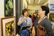 Meredith Ching, left, senior vice president of government and community relations for Alexander and Baldwin and 1974 Punahou alumna and Allene Suemori, 1966 Punahou alumna, look at Leighton Lam's mixed media art piece in the art gallery at the Punahou Carnival.