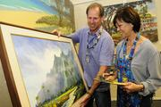 Scott Bradley, owner of Bradley Properties, helps at the Punahou Carnival as a porter at the art gallery as Meredith Ching, right, senior vice president for government  and community relations at Alexander and Baldwin, looks over an painting by artist Michael Powell.