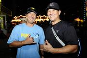 Sean Matsumoto, left, firefighter with the Honolulu Fire Department and Noland Terayama, owner of Ted's Wiring, 1991 alumni, volunteering at the Punahou Carnival.