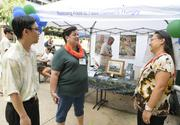 Kuulei Williams, center, executive director of Aloha Harvest, talks with Justin Yamauchi, left, and Davelyn Pao of Meadow Gold Dairies at the Aloha Harvest food drive and agency fair at Bishop Square. Meadow Gold Dairies is one of the nonprofit's major food donors.