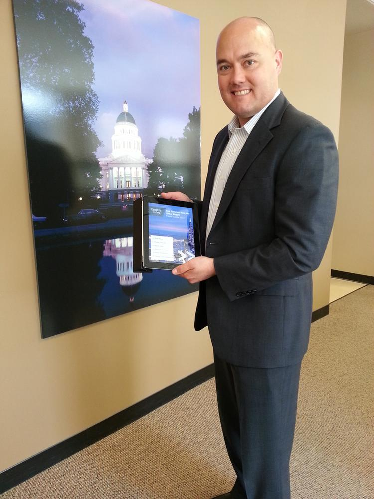 Cassidy Turley broker Chad Cook shows off the new iPad app for the commercial real estate brokerage. The app gives users the ability to compare markets, something that's not as easily done on the regular website.