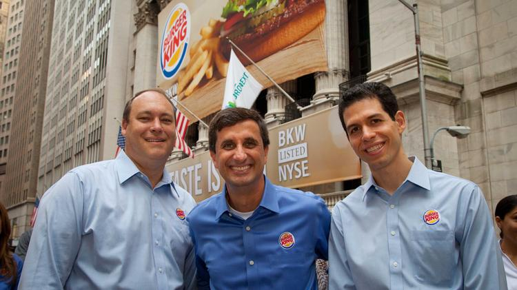 Burger King Corp.'s Steve Wilborg, President; Bernardo Hees, CEO and Daniel Schwartz, CFO, pose outside the NYSE façade adorned with a Burger King banner in celebration of the company's first day of trading on the New York Stock Exchange in June 2012.