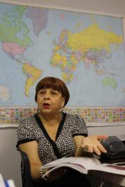"""Tampa Language Center Director and teacher Eva Velez, sits in on an English class and talks about business practices around the world. """"We go with the economy of the United States,"""" she said of her school's business."""