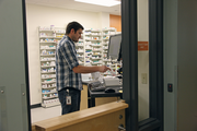 A pharmacist inputs prescription data at Old Town Clinic.