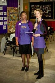 As Cradles to Crayons executive director Sharon Reilly looks on CEO and founder Lynn Margherio welcomes the 85 local business executives who volunteered at the Cradles to Crayons President's Day Celebration of Service.