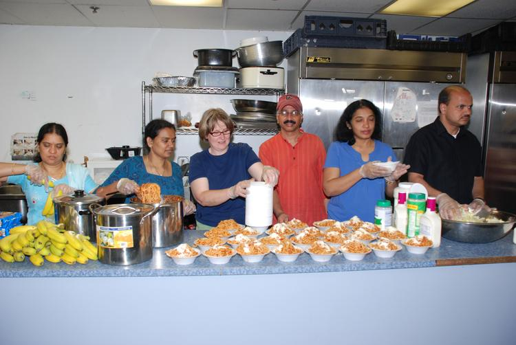 Charitable activities at Halcyon Solutions include serving meals to homeless people. Company CEO Mohan Viddam is in the red shirt.