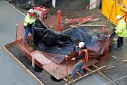 Crews lay a tarp Wednesday over a hole where a mammoth tusk from the Ice Ages was found during construction work Tuesday. Crews continued work Wednesday morning at the site at Pontius Avenue North and Mercer Street in Seattle's busy South Lake Union area.