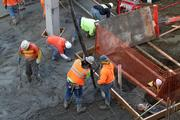 Crews lay concrete near where an ice-age mammoth tusk was discovered on a construction site in Seattle's South Lake Union. The section with the tusk is behind the orange fence. Burke Museum experts say the decision on what to do with the tusk will be made by the landowner, a commercial real estate company.