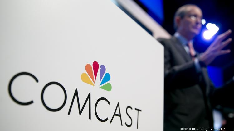 The Comcast logo is seen as Brian Roberts, chairman and chief executive officer of Comcast, speaks during a news conference at the 2013 National Cable and Telecommunications Association (NCTA) Cable Show. Comcast is reportedly set to announce a deal to purchase Time Warner Cable.