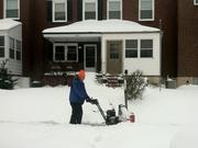 A man uses a snow blower to clear a sidewalk on Park Haven Road in Dundalk.