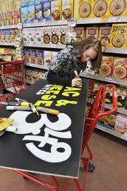 Naomi Torres, crew member at Trader Joe's on South University, makes a sign in preparation for opening on Friday.