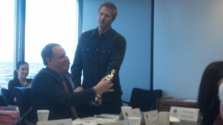 "Filmmaker Daniel Junge shows the Oscar he won for the documentary ""Saving Face"" to Jeff Kraft of the Colorado Office of Economic Development and International Trade."