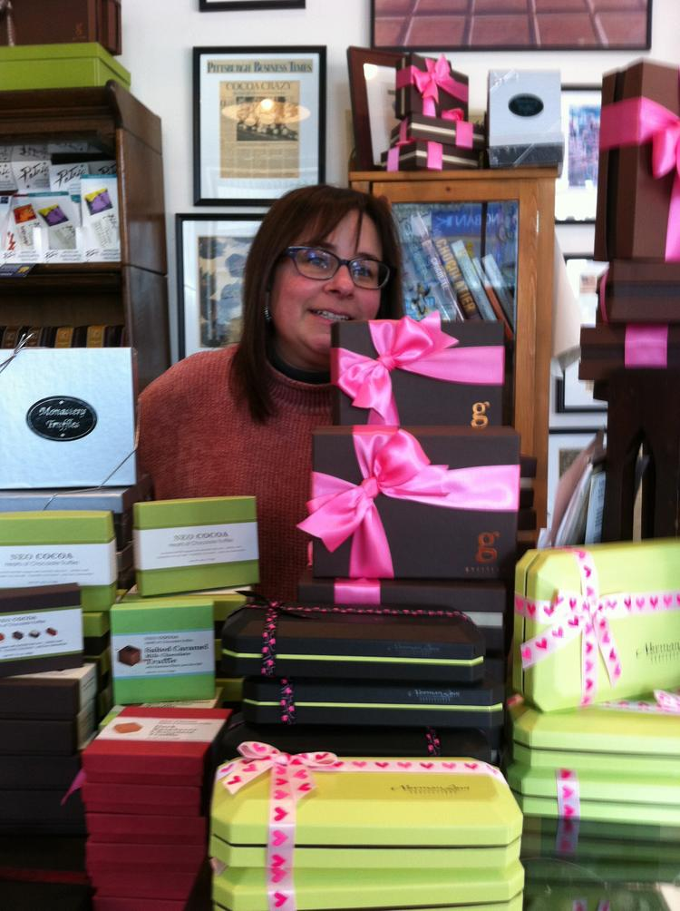 Amy Rosenfield, owner of Mon Aimee Chocola in Pittsburgh's Strip District, behind stacks of Valentine's Day chocolates.