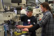 Students Ngu Nguyen (left) and David Klinger work on a manual mill during a Precision Machining II class in the AJAC Machining Apprenticeship Program at Renton Technical College. Nguyen, who works by day as a machinist at Fatigue Technology Inc., says he has been a machinist for 28 years, but is attending school to earn a journeyman license.