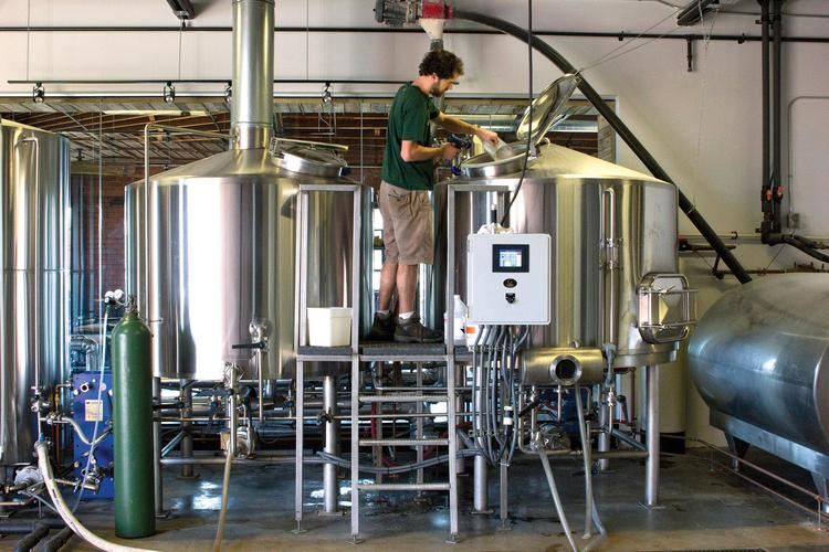 Triple C's head brewer, Scott Kimball tends to two large boilers.