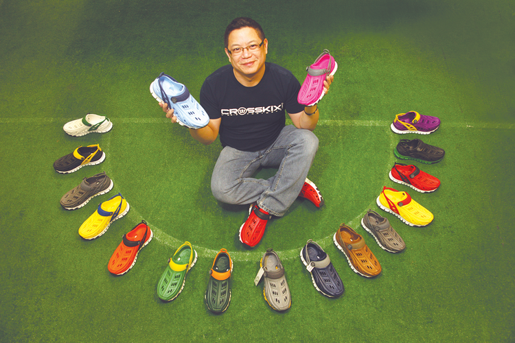 """Arthur Seto, operations director for Crosskix, showcases the startup's multi-colored footwear. """"We're going to create a huge array of colorways,"""" Seto said."""