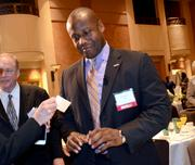 Lynx CEO John Lewis Jr. exchanges business cards before the panel begins.