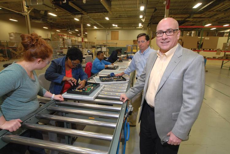 Stephen Galloway, in sport jacket, with workers at ESP/SurgeX in Knightdale.