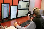 """Helmsderfer sits in front of his five computer monitors, which his employees have dubbed """"The Matrix."""""""