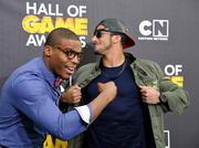Cam Newton (left) takes a jab at rival Colin Kaepernick as another Superman pose breaks out between the two NFL quarterbacks. The players taped a Cartoon Network awards show this weekend in California.
