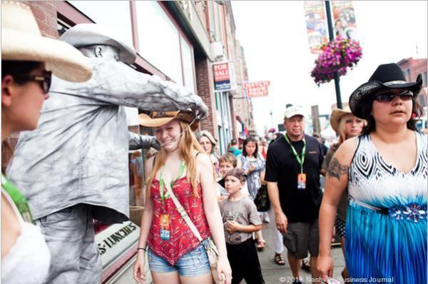 Tourists receive beads from the Silver Cowboy, John Casey, during this year's CMA Music Festival.