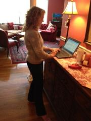 """Dorle Webster, the wellness director at Banyan Consulting Group Inc., figured out that the dining room buffet is the perfect height for her """"at-home"""" stand-up desk."""
