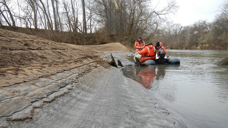 Tom Augspurger (left), contaminants specialist for the U.S. Fish and Wildlife Service, takes a core sample of coal ash on Feb. 8 on the banks of the Dan River. Augsperger is shown here with John Fridell, also with the federal agency, and Rick Smith of Duke Energy (NYSE:DUK). Photo by Steve Alexander, USFWS