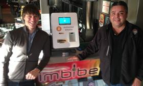 Eric Stromberg, Enchanted Bitcoin founder (left) poses with his Bitcoin ATM at Imbibe, the bar owned by Wes Golden (right).