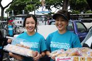 Carrie Okinaga, right, senior vice president and general counsel for First Hawaiian Bank, with Lauren Seu passing out water and food to the military participatants in the Kaiser Permanente Great Aloha Run.