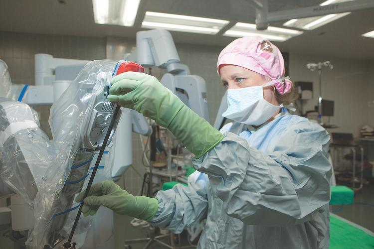 Operating room technician Catherine Wallace sets up a da Vinci surgical system for training at Niagara Falls Memorial Medical Center. Since the hospital added the system in 2012, hundreds of procedures – the majority were gynecological surgeries – have been performed with the equipment.