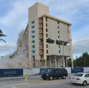 The last part of the Howard Johnson Hotel begins to fall.