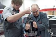 James Wyatt, instructor in the automotive classes at JCTC, held a clamp steady for Chris Aken, left.