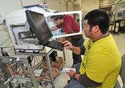 James Ang (in yellow) and Larry Barao, who are both technicians, program a machine at Precision Valve & Automation Inc., in Colonie.