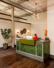 Garrison Hullinger Interior Design converted former storage space on the second floor of the Rejuvenation store in Portland's Central Eastside Industrial District into its working studio. A studio assistant at the reception area welcomes Rejuvenation shoppers who come up to the space.