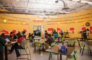 """The circular employee break room creates a community feel. The brightly colored room is surrounded by yellow walls that offer definitions of the word """"community,"""" along with illustrations of people doing activities outside."""