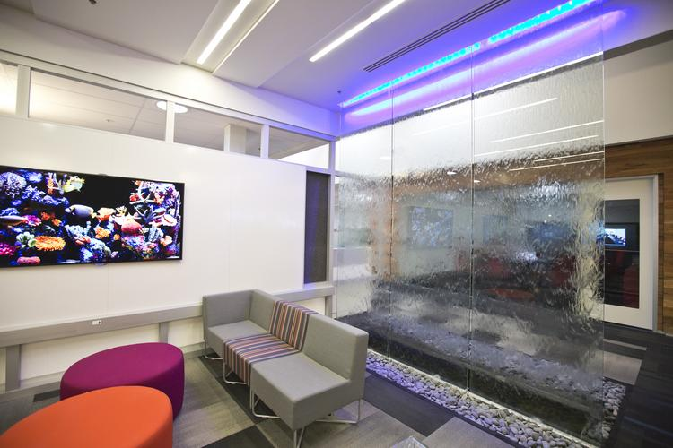 A water wall feature provides additional ambient noise. The flat screen with images of exotic fish and brightly-colored furniture accents are just for ambiance.  Click the image for a full tour of the recently-overhauled Surf City tech campus.