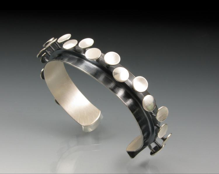 Theresa Carson handcrafts all of her jewelry in her Baltimore studio. She has been making and selling her work for 21 years.  The work is about juxtaposing different surfaces: polished, matte, dark, light. The patterns are all done by hand with a sharp scribe.