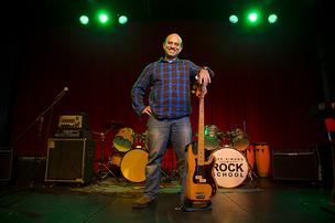 Dave Simon poses for a photograph on a stage at his School of Rock.