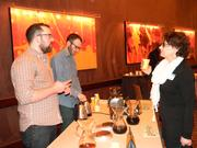 Colectivo Coffee employees Cody Kinart, left, and Scott Lucey offer samples to attendee Toni Spott.