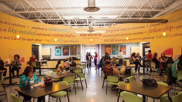 """The circular employee breakroom at Accent Marketing Services creates a community feel, said Kelly Hilton, vice president of corporate communications. The room is filled with bright colors and definitions of the word """"community,"""" along with illustrations of people doing activities outside."""