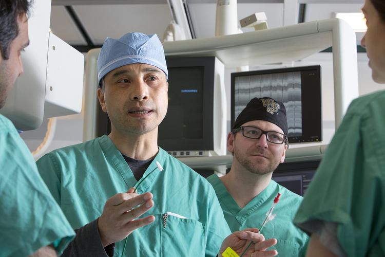 Dr. David Zhao, center, executive director at Wake Forest Baptist Medical Center Heart and Vascular Center, discusses cardiology procedures as Steven Heatherly, a second-year fellow, looks on.