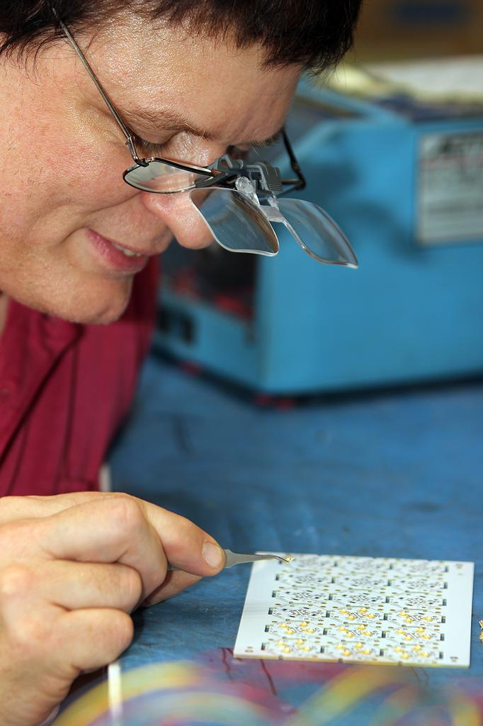 Mark Rutter, senior electronic technician, mounting LEDs and resistors onto a light machine board.