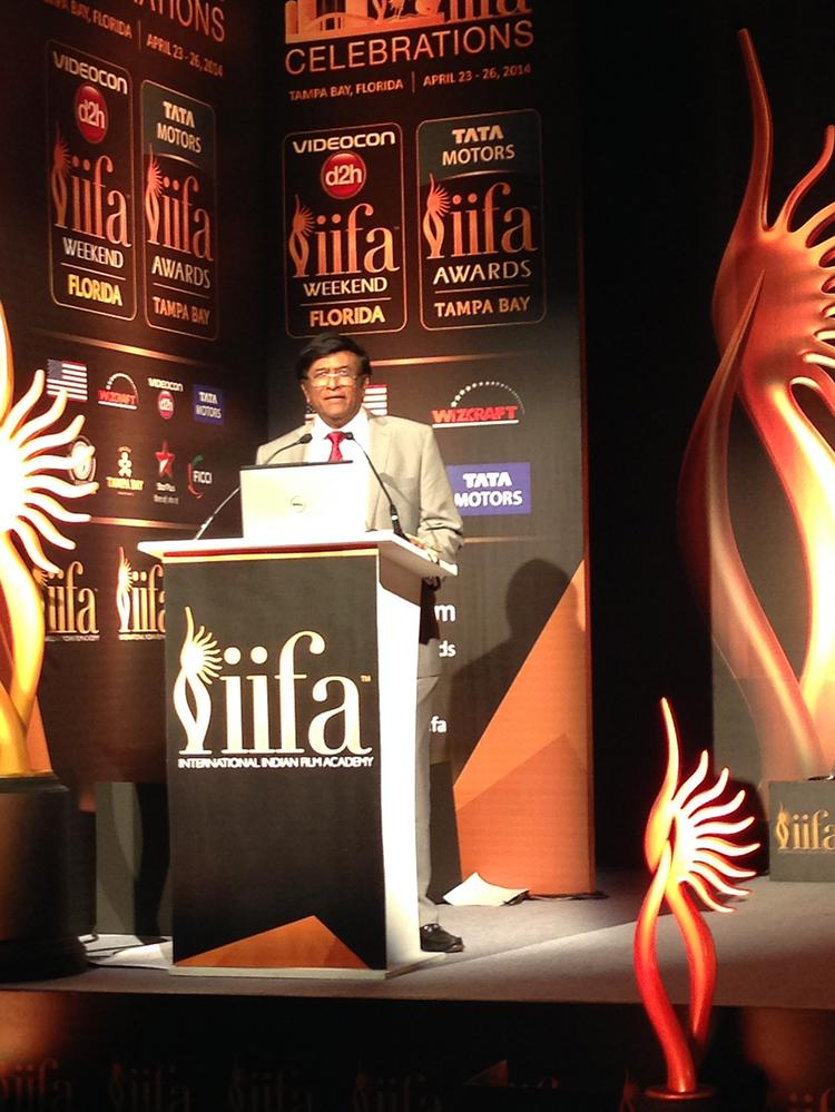 Dr. Kiran Patel on stage at an IIFA media conference.