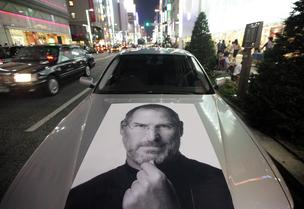 A car bearing a photograph of Steve Jobs, late chief executive officer of Apple Inc., is parked outside the Apple store at night in the Ginza district of Tokyo, Japan, on Thursday, Sept. 20, 2012 as Apple's iPhone 5, which featured a bigger screen, faster chip and a lighter body was released.