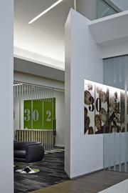 """A view looking through the entry area into the meeting space includes field markings referenced in the glass film pattern and """"turf green"""" accents providing a pop of color."""