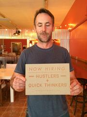 """Corner Taco owner Chris Dickerson holds his now hiring sign. Looking for """"hustlers and quick thinkers,"""" he said, is part of his branding."""