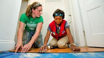 A Lowe's (NYSE:LOW) employee works alongside a Habitat volunteer on a project in the Smallwood neighborhood of Charlotte.