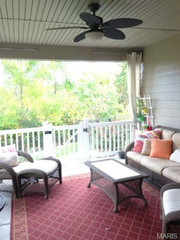 12568 Grandview Forest Drive: A covered porch features a ceiling fan and curtain.