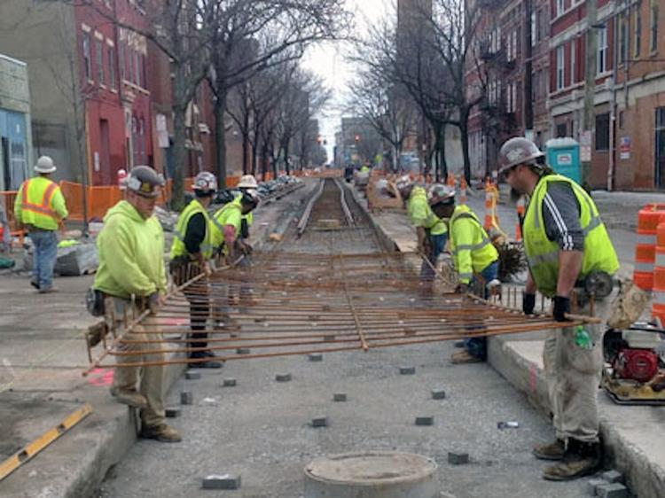 Crews install rebar on the excavated track slab for the streetcar.