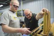 Lee works with his son Kyle at the lathe.